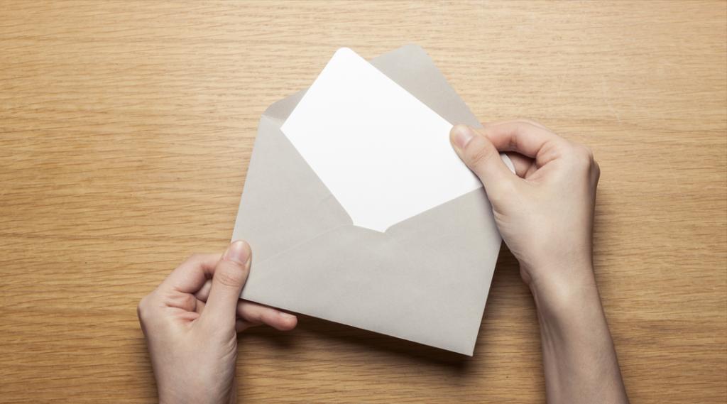 Uma mão feminina (mulher) segurar (aberto) um envelope e cartão postal na mesa de madeira, vista superior no estúdio.