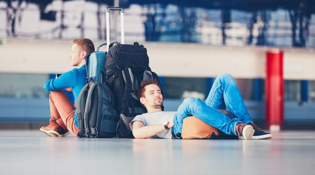 Dois amigos viajando juntos. Viajantes à espera na área de partida do aeroporto para o seu voo de atraso.