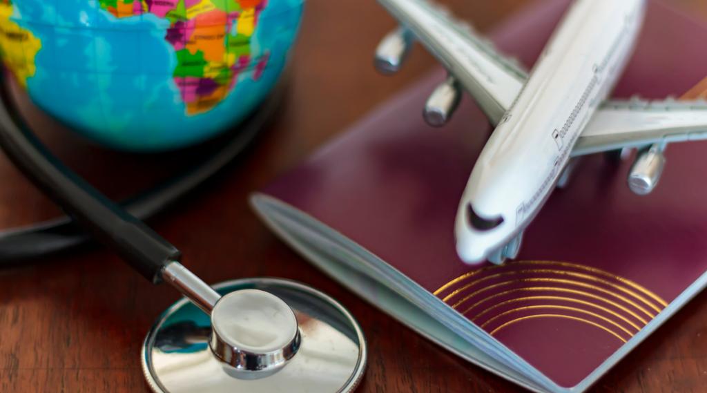 Cuidados de saúde globais e o conceito de seguro de viagem. Estetoscópio de passaporte, avião e globo na mesa de madeira