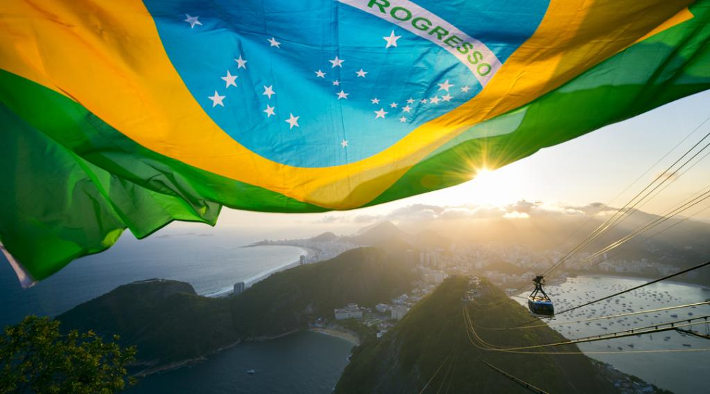 Bandeira brasileira brilha acima do horizonte dourado da cidade no Pão de Açúcar Pão de Açúcar no Rio de Janeiro Brasil