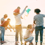 Famílias felizes voando com pipa e se divertindo na praia - Pais brincando com crianças ao ar livre - Conceito de viagens, amor e férias