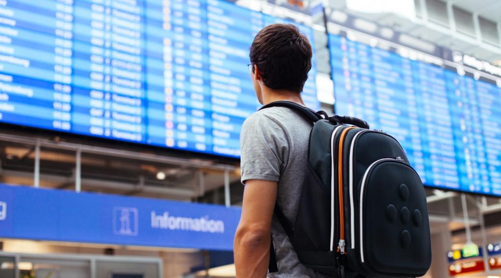 Jovem com mochila no aeroporto perto horário de voo