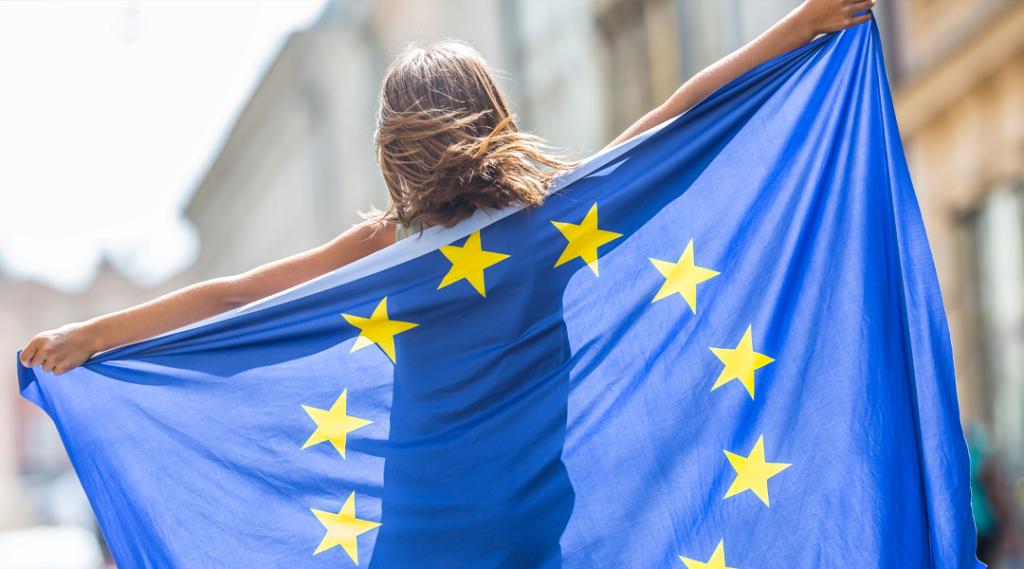 Bonito jovem feliz com a bandeira da União Europeia.