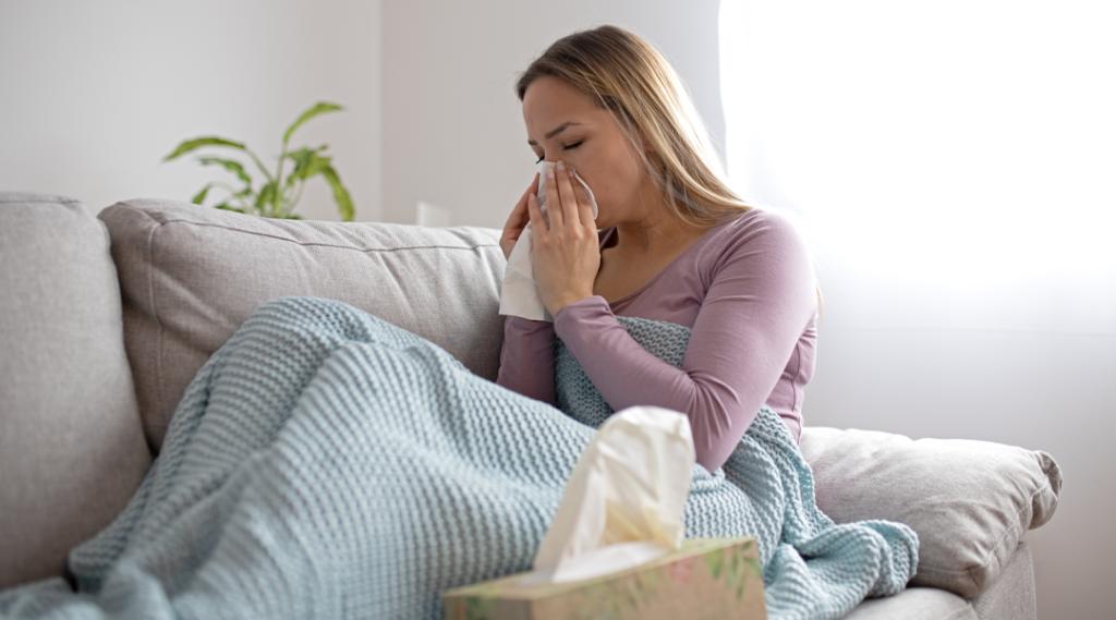 Mulher doente assoar o nariz, sentado debaixo do cobertor. Mulher doente com infecções sazonais, gripe, alergia, deitada na cama. Mulher doente, coberta com um cobertor deitado na cama com febre alta e gripe, descansando.