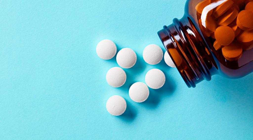 Brancos médicos comprimidos e comprimidos derramando fora de um frasco de drogas. Macro de cima para baixo com espaço de cópia. Seguro Viagem Internacional