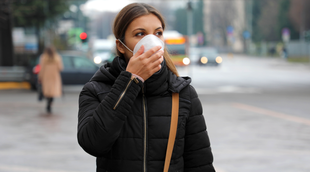 Coronavírus pandêmico COVID-19 Mulher na rua usando máscara facial protetora para disseminação do vírus da doença SARS-CoV-2. Menina com máscara protetora no rosto contra a doença de coronavírus 2019.