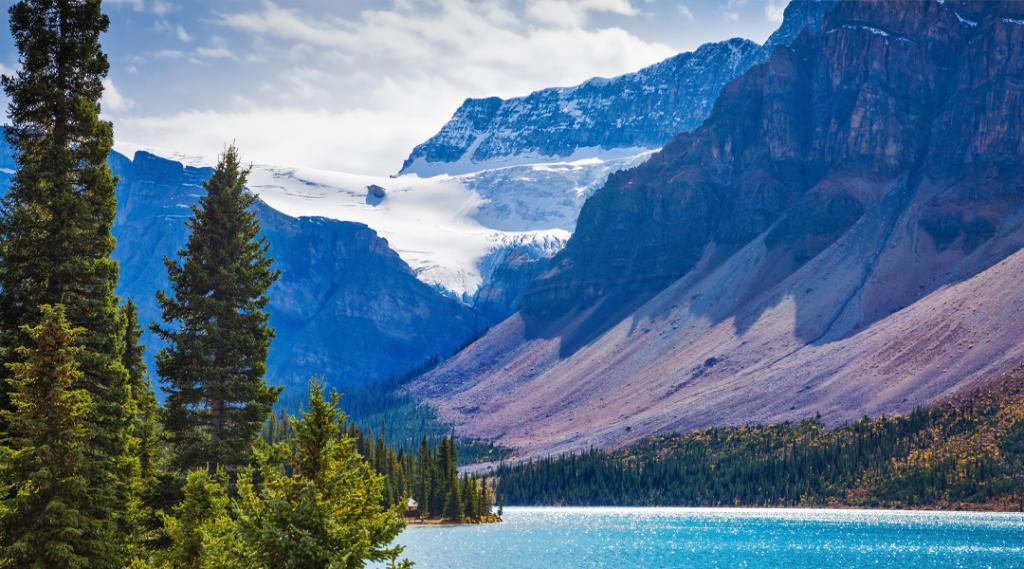 """Dia ensolarado de outono para as montanhas rochosas do Canadá em Lake Bow. O lago é cercado por pedras e abetos. Geleira """"Crowfoot"""" brilha na luz do sol"""
