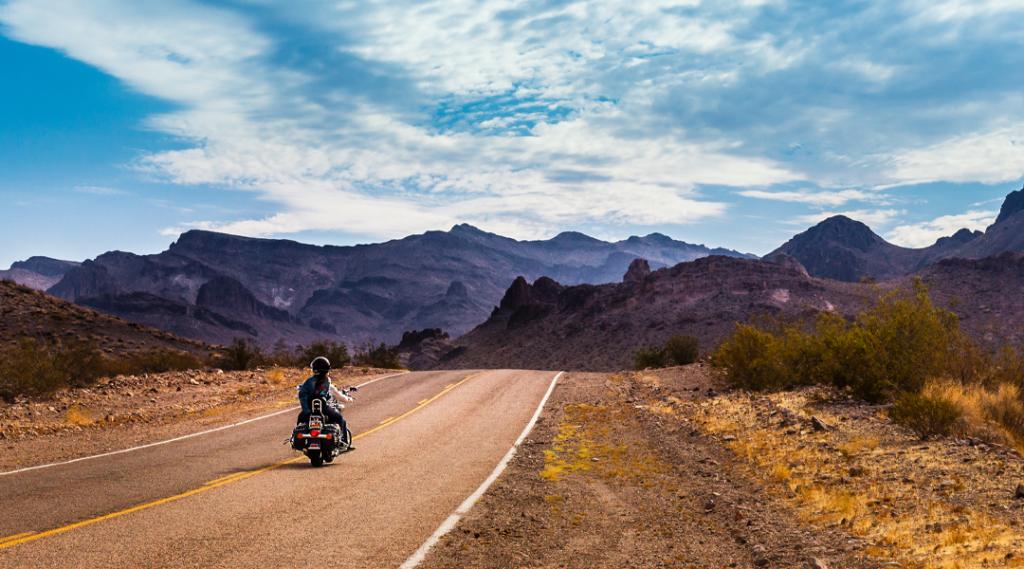Motociclista dirigindo na estrada na lendária Rota 66 para Oatman, Arizona.