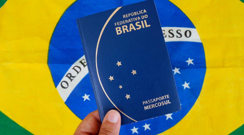 Tradução: República Federativa do Brasil (República Federativa do Brasil). Mão de uma mulher segurando o passaporte brasileiro sobre a bandeira brasileira. Conceito de viagens.