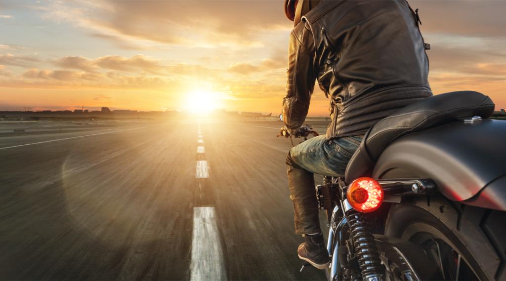 Motorista de motocicleta andando sozinho em rodovia de asfalto. Fotografia ao ar livre. Conceito de viagens e esporte, velocidade e liberdade. Seguro viagem américa do sul