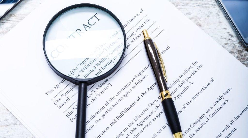 imagem de lupa e uma caneta em um contrato para ser assinado