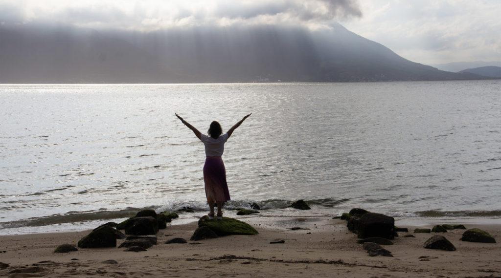 imagem de uma mulher na praia de braços abertos