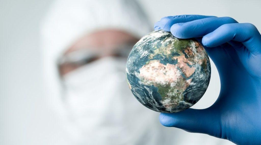profissional da saúde desfocado na imagem segurando um globo terrestre. Seguro viagem tem cobertura na pandemia?