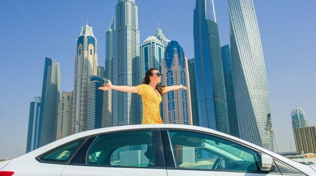 mulher no teto solar de um veículo em movimento