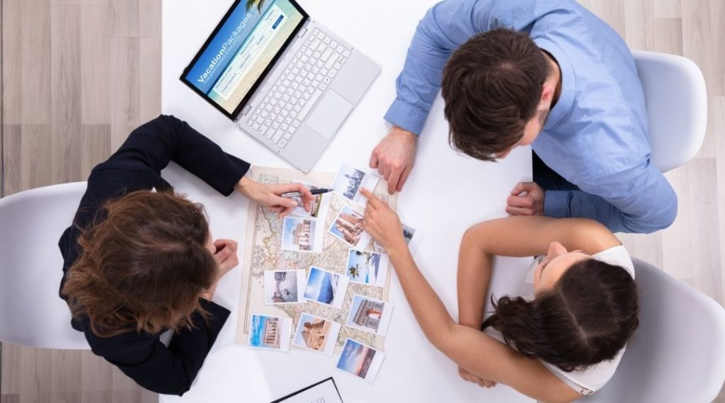 Jovem casal consultando com o agente de viagem como viajar barato
