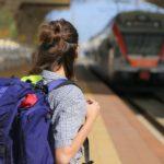 garota mochileira esperando o trem