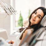 mulher sentada em cadeira odontológica, despesas odontológicas