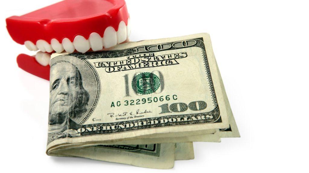 dentadura abocanhando notas de 100 dólares. Despesas Odontológicas