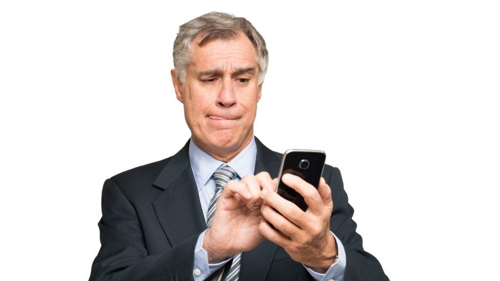 homem de cabelo grisalho e com terno, acionando pelo celular a cobertura de despesas odontológicas do seguro viagem