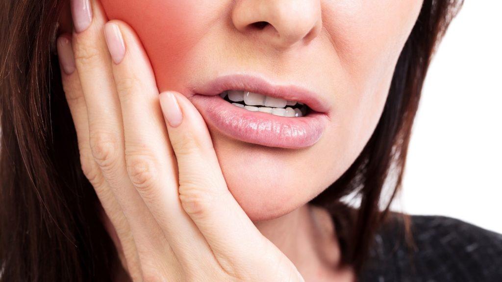 mulher com mão no rosto com dor de dente. Despesas odontológicas.
