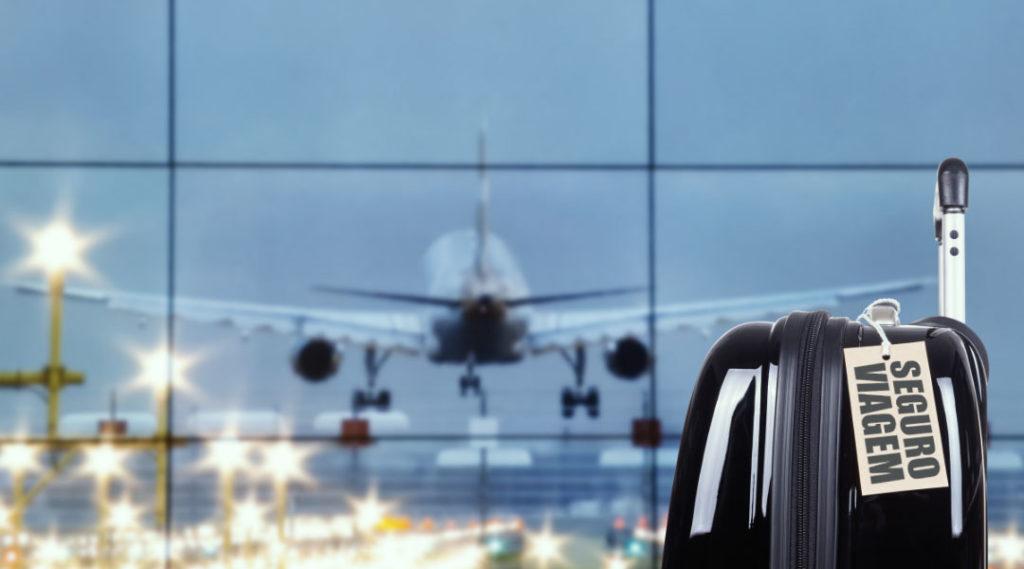 avião ao fundo e mala de viagem em foco com etiqueta de seguro viagem