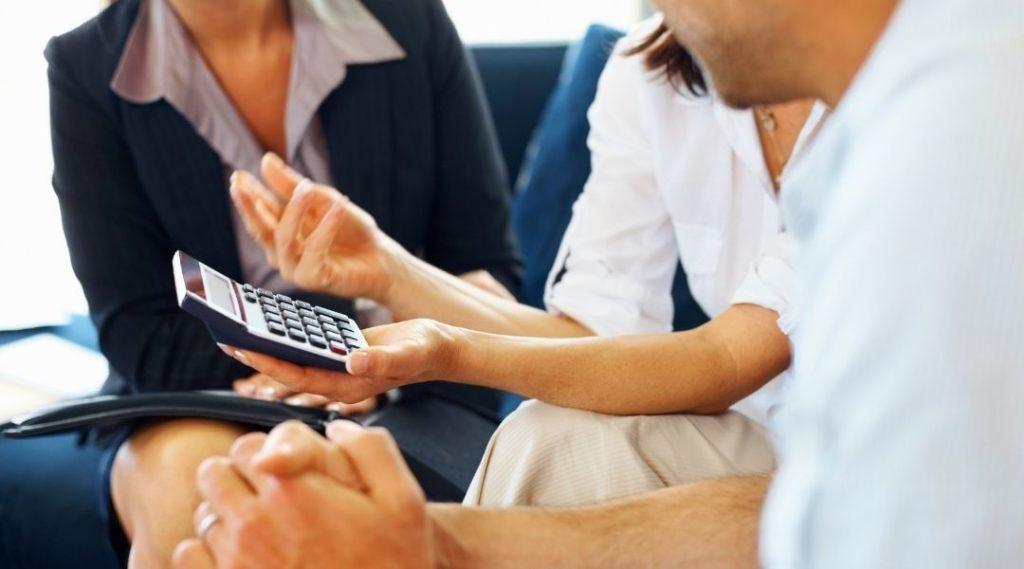 Casal discutindo questões financeiras com o consultor. Seguro viagem
