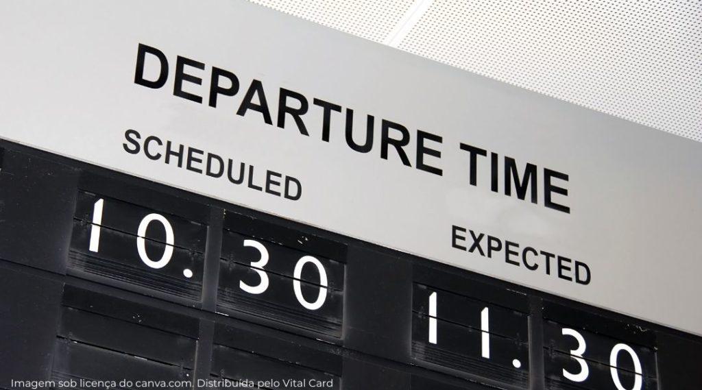 terminal de aeroporto mostrando atraso de voo por uma hora, saída inicial 10h30, saída prevista 11h30