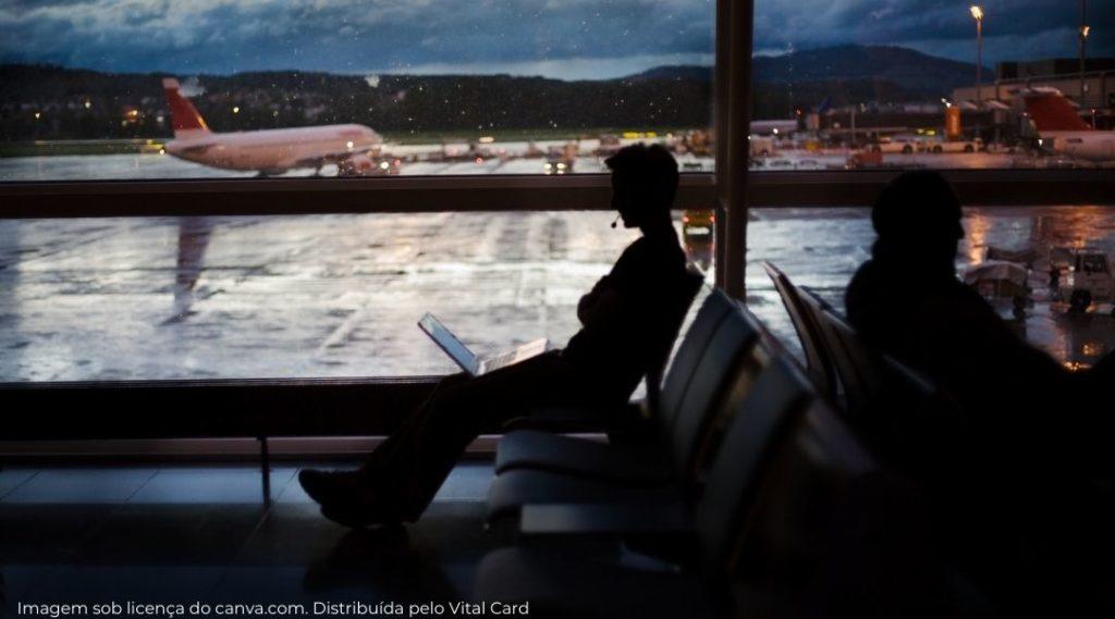homem esperando 2h sentado no terminal do aeroporto com notebook no colo, entediado, atraso de voo