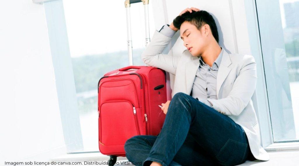 homem sentado no chão encostado em sua mala no aeroporto. Entediado e estressado, quase dormindo.