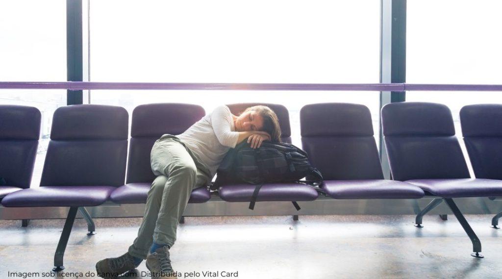 mulher deitada em banco do aeroporto usando sua mochila como travesseiro.