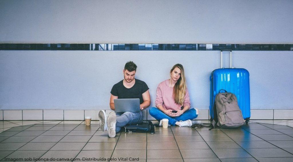 Casal jovem sentado no chão do aeroporto esperando por causa de voo atrasado. Homem está com notebook no colo, mulher olhando entediada com mala e mochila ao seu lado