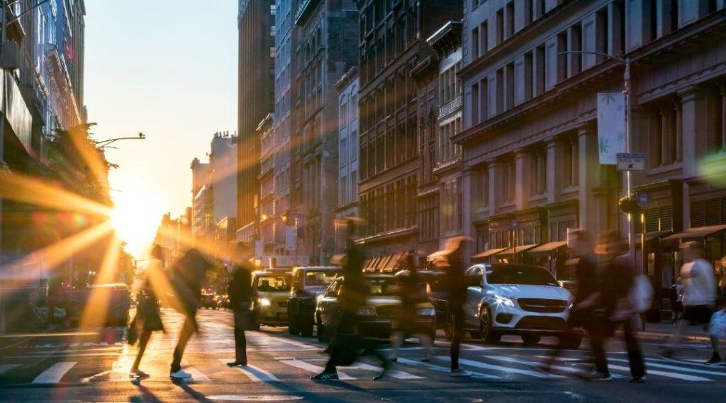 imagem de uma rua movimentada em Nova York, carros parado esperando o sinal abrir enquanto os pedestres atravessam pela faixa.