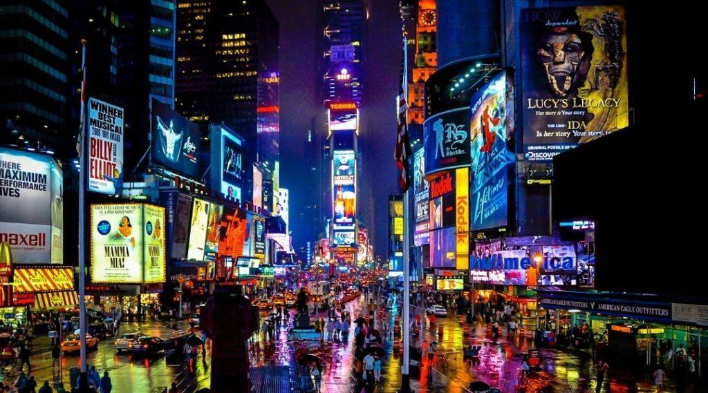 foto da rua Time Squares a noite, a rua está molhada, diversas pessoas passeiam com as gigantescas placas de neon em volta nos prédios. O que fazer em Nova York
