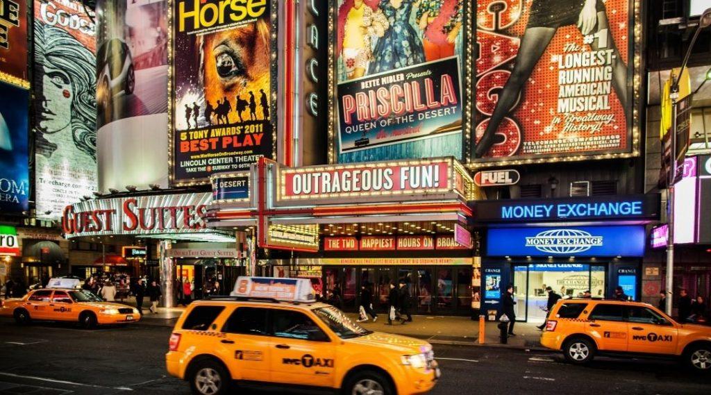 Foto de um teatro da Broadway a noite, com diversos taxis amarelos, classicos de Nova York. O que fazer na cidade