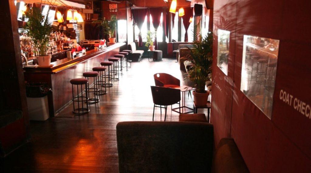 Foto de um bar de Nova York durante o dia. O bar possui paredes vermelhas e um balcão com diversas banquetas.