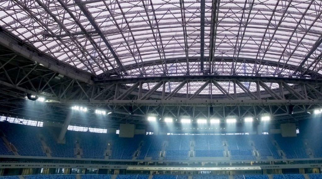 Foto de um estádio de futebol americano em Nova York vazio. Com as luzes acesas. O estádio possui o topo aberto com grandes e milhares de bancos azuis.