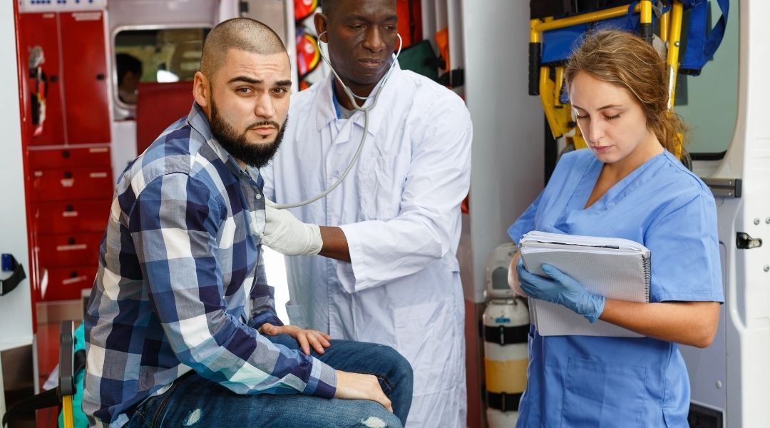 homem jovem em ambulância sendo consultado por doutor e enfermeira, regresso sanitário