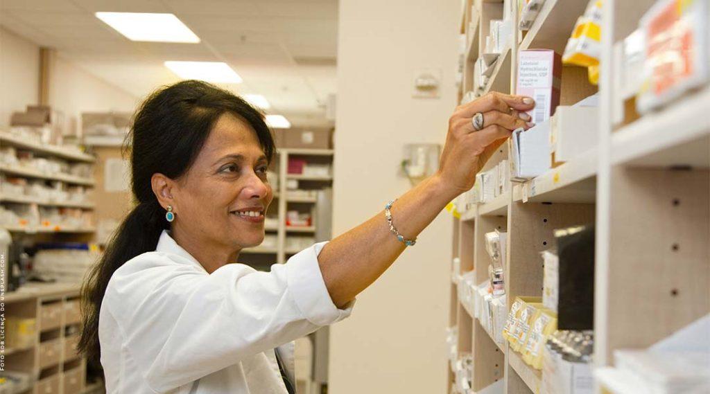 farmacêutica sorrindo em uma farmácia enquanto procura um remédio em uma prateleira. Despesas farmacêuticas.