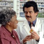 farmacêutico com remédio na mão conversando com mulher negra idosa, os dois estão em uma farmácia e sorriem