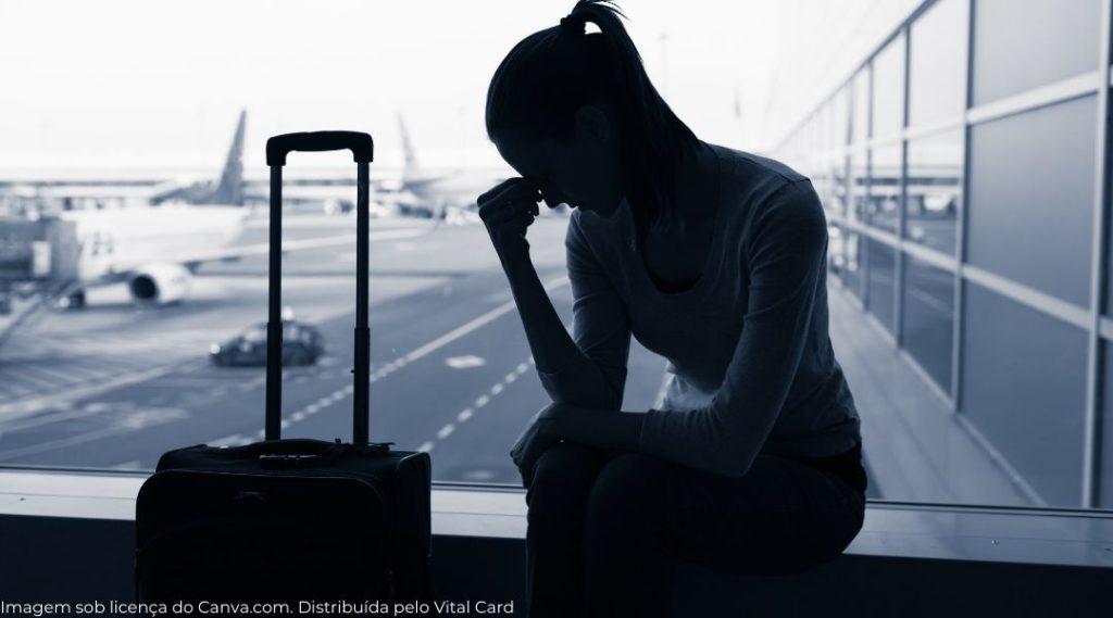 Silhueta de uma mulher preocupada em um aeroporto por ter que interromper sua viagem.