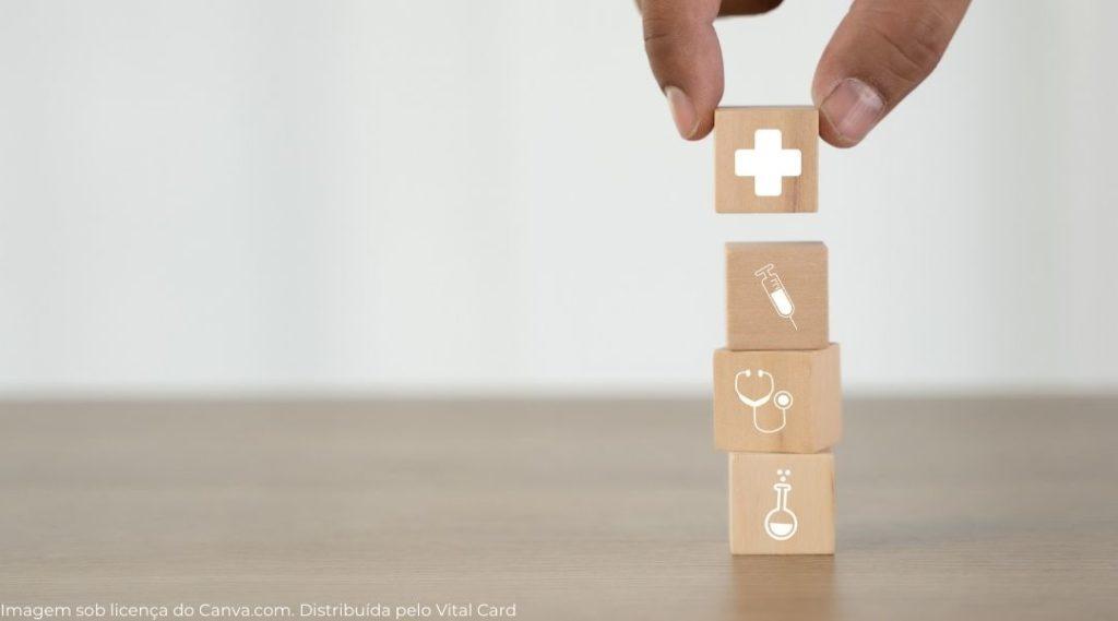 Mão empilhando pequenos cubos de madeira com sinais de saúde estampados