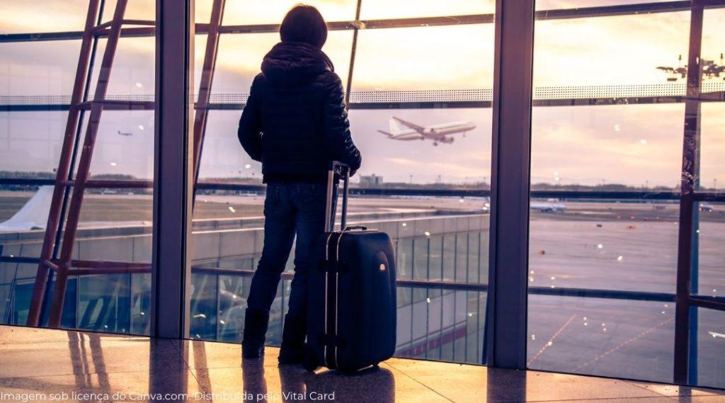 Silhueta de pessoa no aeroporto que teve sua viagem interrompida olhando os aviões decolarem