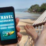 pessoa relaxada deitada em uma rede numa praia com o celular na mão vendo o aplicativo do seguro viagem e suas coberturas