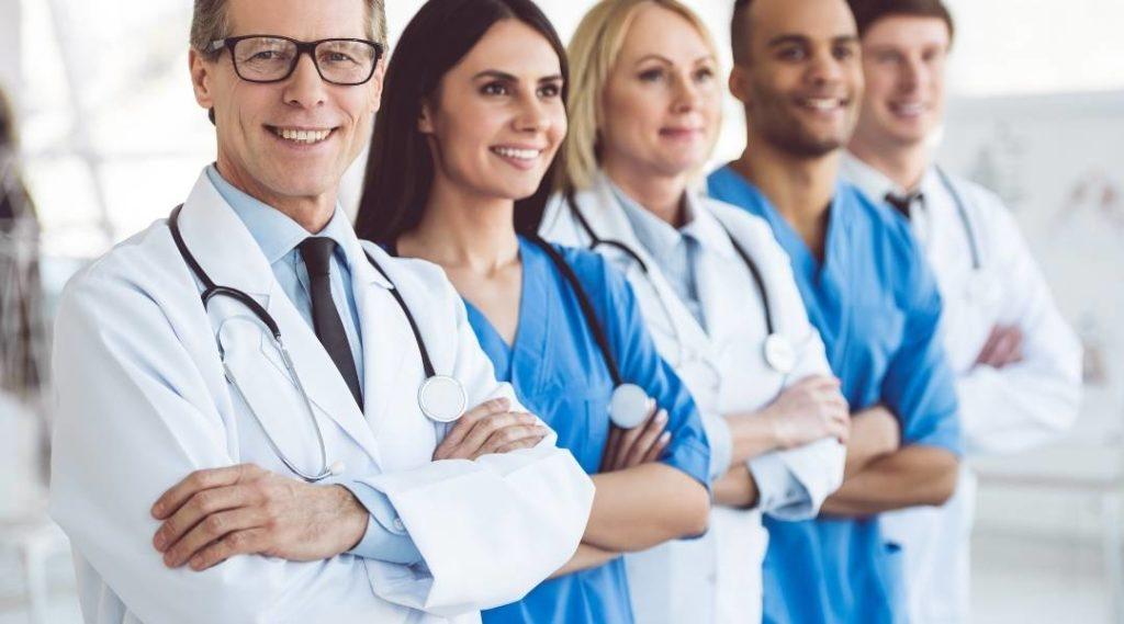 Diversos médicos e médicas em uma fila com braços cruzados e sorrindo.