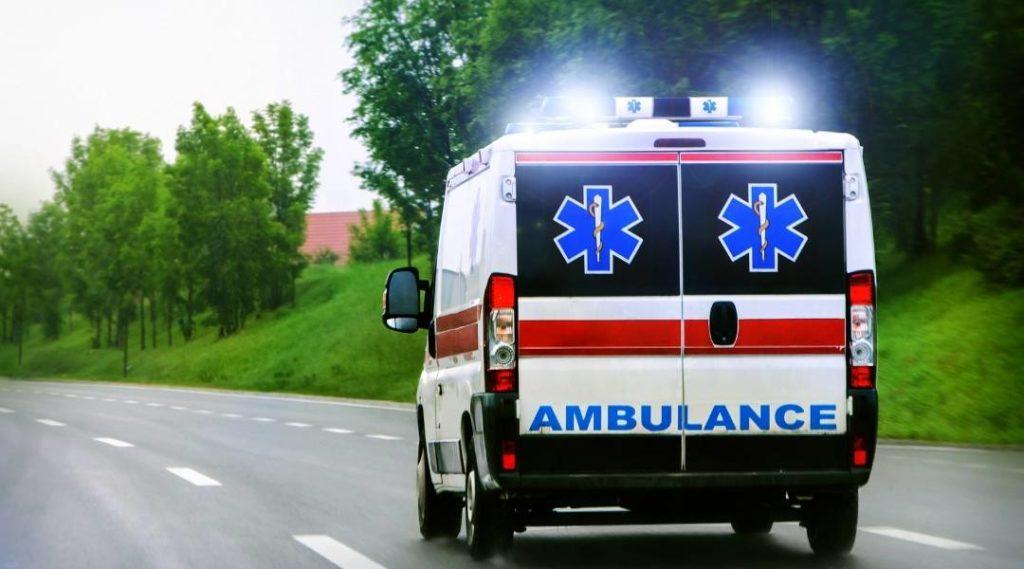 Ambulância com sirenes ligadas indo ao hospital em uma estrada.