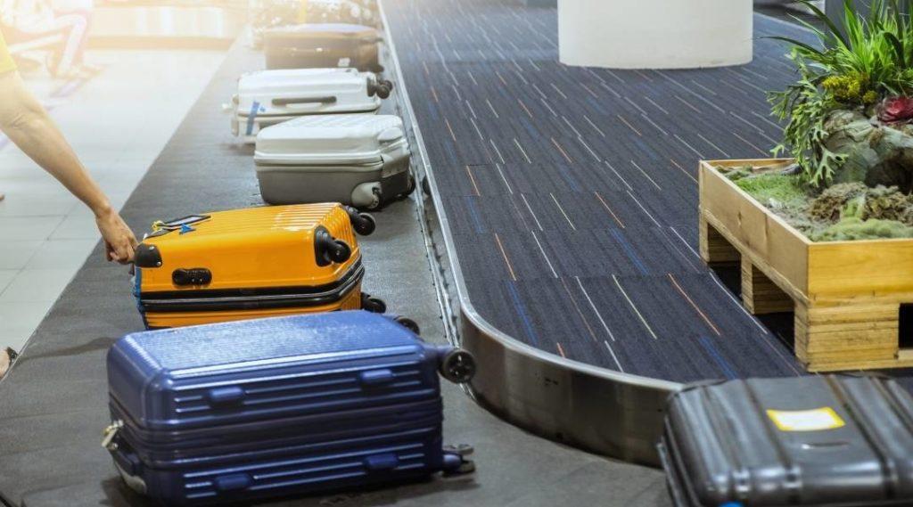 Esteira de aeroporto com diversas bagagens e uma mão pegando uma das bagagens. Coberturas do seguro viagem