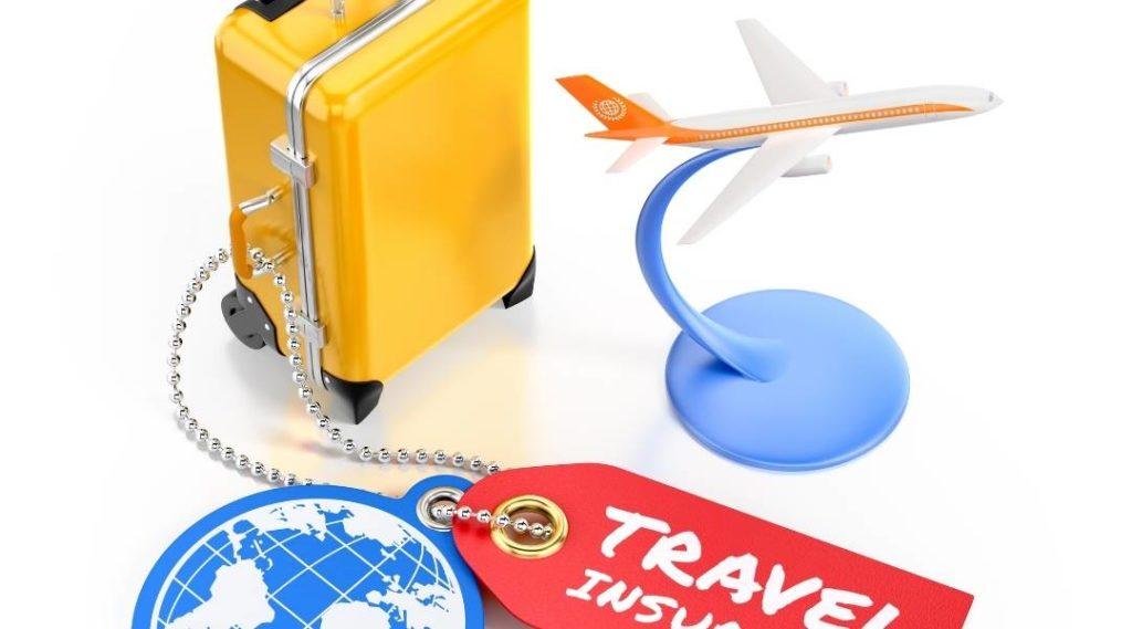 """Miniatura de mala e avião em fundo branco,com um adesivo que diz """"seguro viagem"""" em inglês. Cobertura do seguro viagem."""