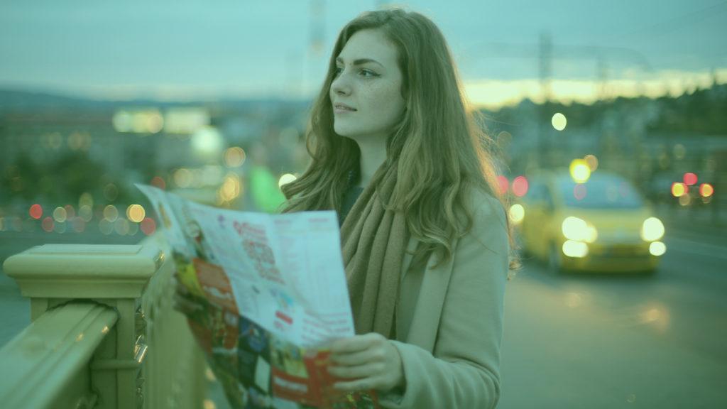 Planejamento de viagem internacional: Mulher em grande cidade com mapa na mão