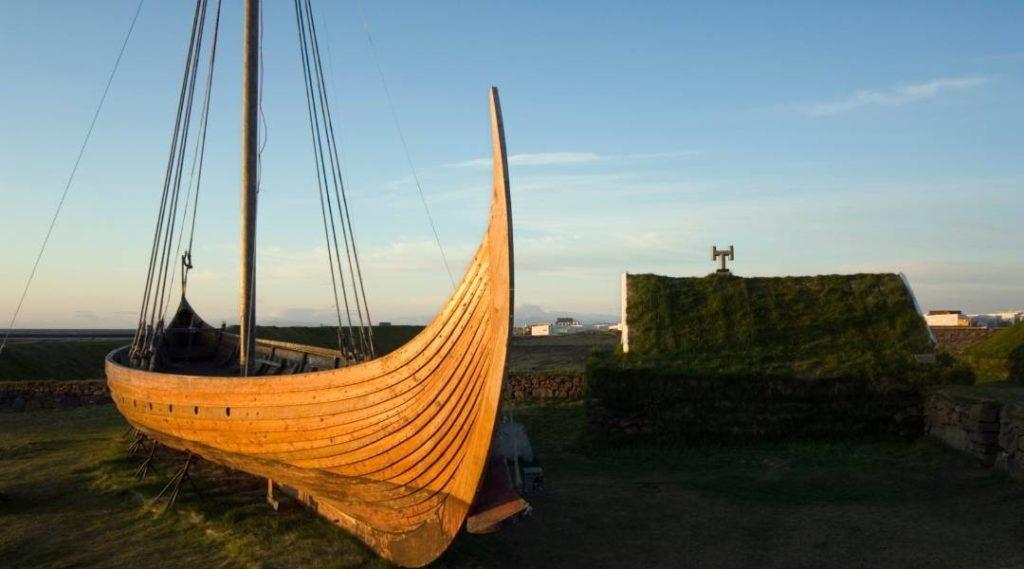Foto de barco viking em primeiro plano, com casa de arquitetura viking no plano de fundo