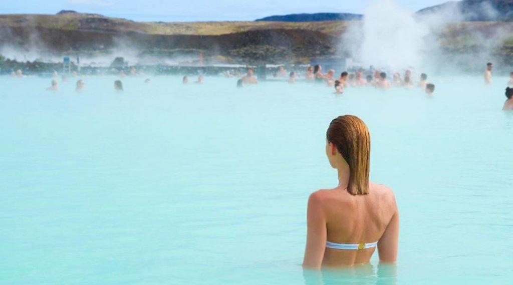 Foto de uma jovem mulher de costas aproveitando um dos melhores pontos turísticos da Islândia, uma de suas fontes geotermais.